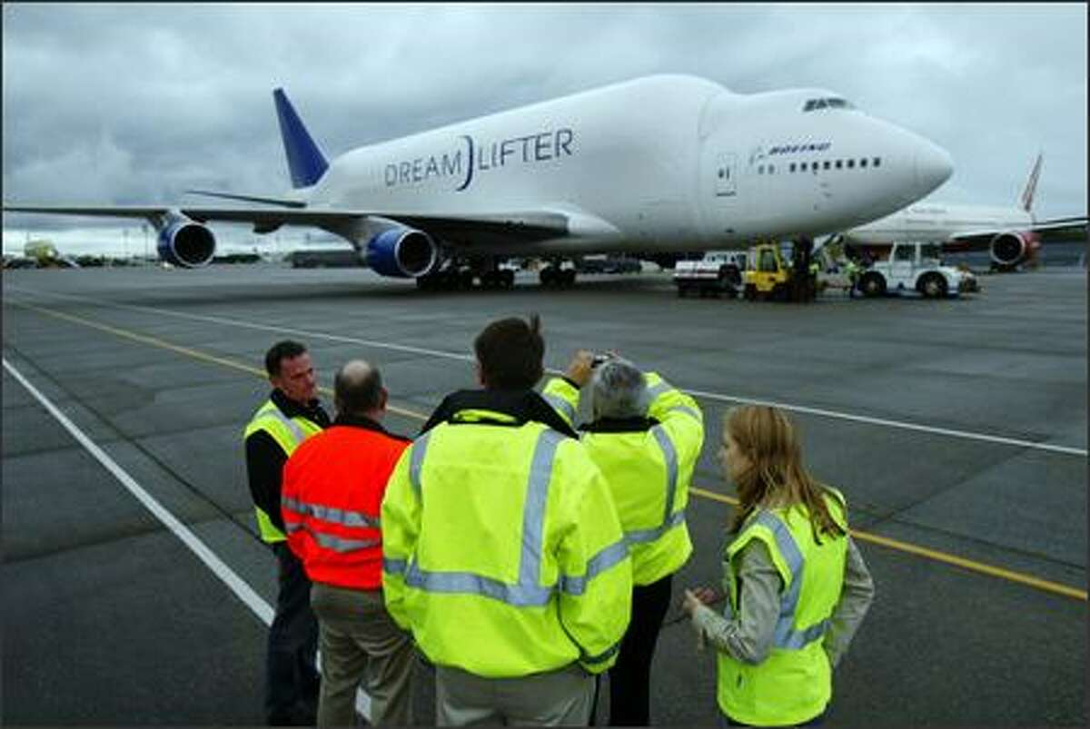 A modified 747, the Dreamlifter, is worked on by crew after landing.