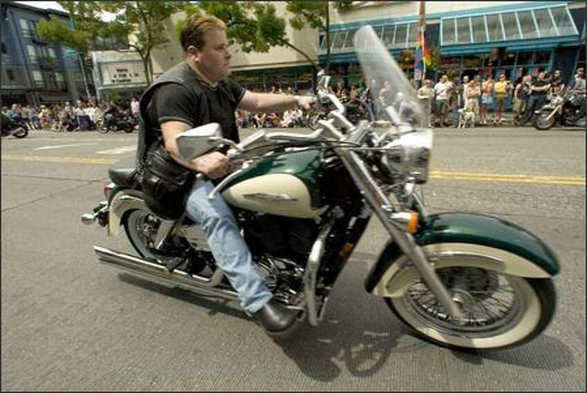 A biker roars past the crowd during the Pride March.