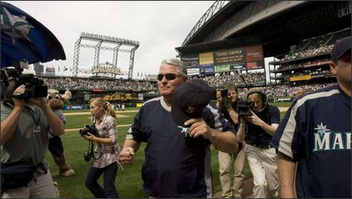 Outgoing Seattle Mariners manager Mike Hargrove pumps his fist and doffs his hat to the fans as the leaves the field after the team defeated the Toronto Blue Joys. It was the team's eighth straight win -- and Hargrove's last game as manager.