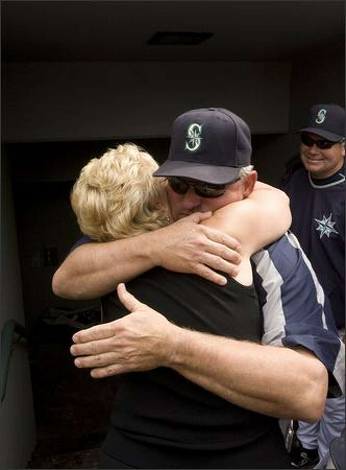 Mariners manager Mike Hargrove hugs his wife, Sharon, at the end of the game Sunday.