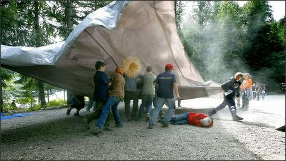 """Dust flies as a group of boys play with a trap as they wait to be """"deployed"""" on a horseback riding trip, at Camp Zanika Lache, near Lake Wenatchee State Park on Wednesday June 27,2007. The summer camp, code named """"Operation Purple,"""" is for children of armed forces members deployed overseas."""