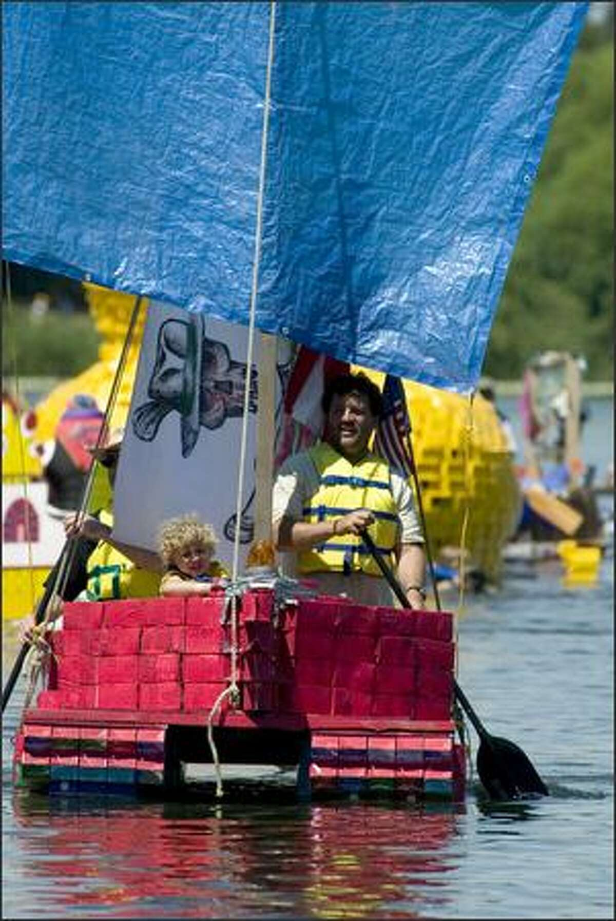 Boaters row towards the finish line in the Seafair Baffle Gab Milk Carton Derby along the southwest shore of Green Lake in Seattle.
