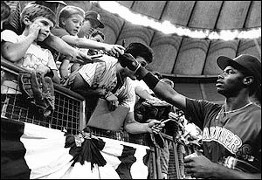 Griffey signs autographs before a game.