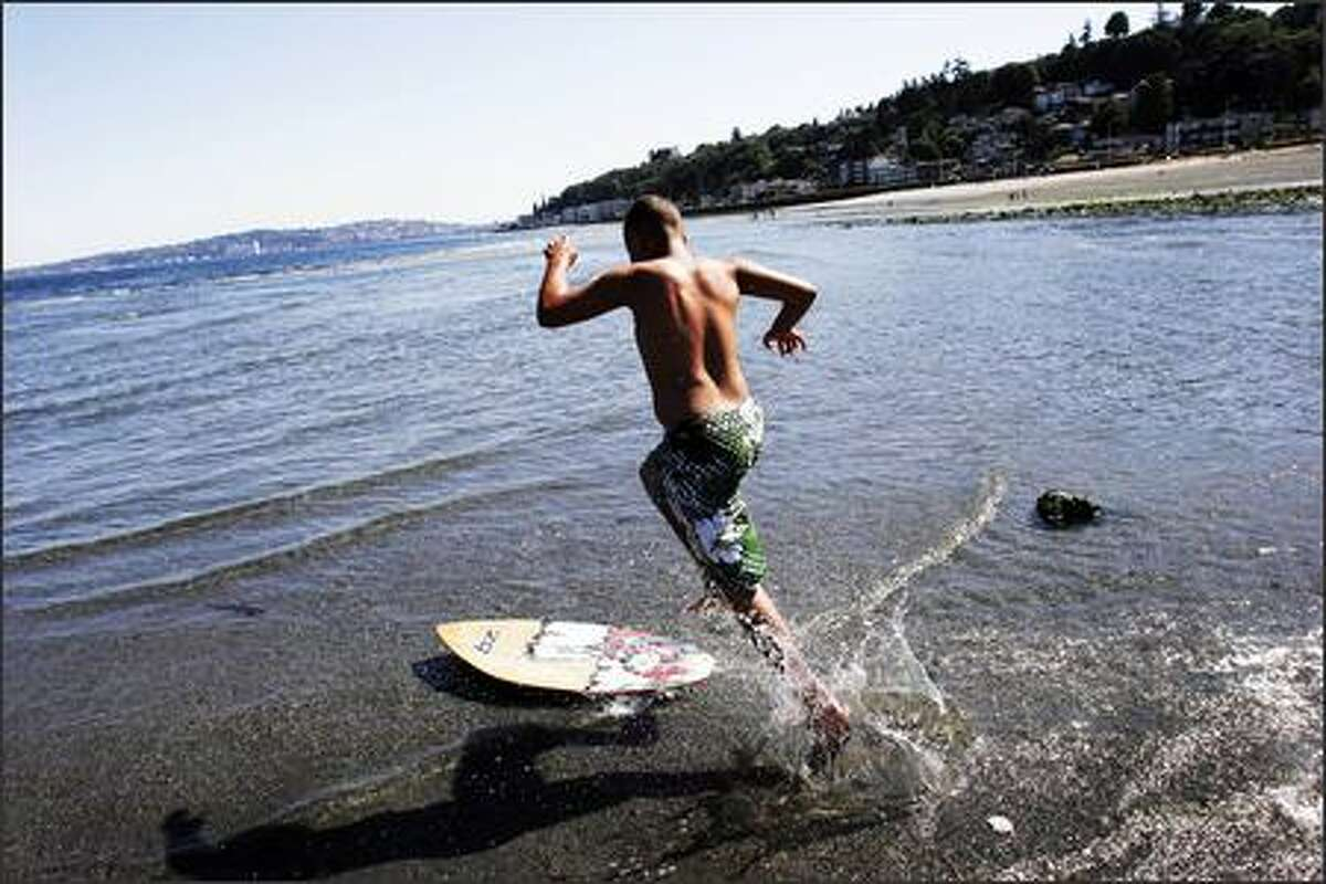 Chandler Reed, 11, of West Seattle skimboards at Alki Beach in Seattle around 10 a.m. on Wednesday. This morning's -2.2 tide facilitated skimboarding, which is done in long steches of shallow water.
