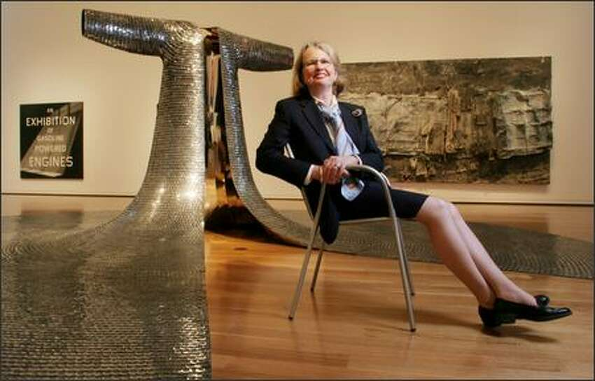 Director Mimi Gates sits in a contemporary gallery surrounded by, from left, Ed Rusha's 1993