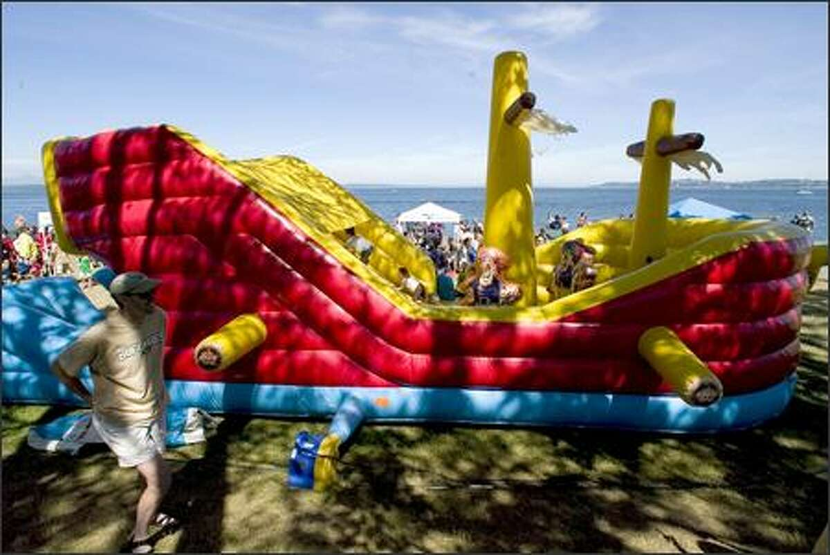 Kids play on an inflatable pirate boat as they wait for the Seafair pirates to storm Alki Beach, kicking off the month-long 58th annual Seafair festival.