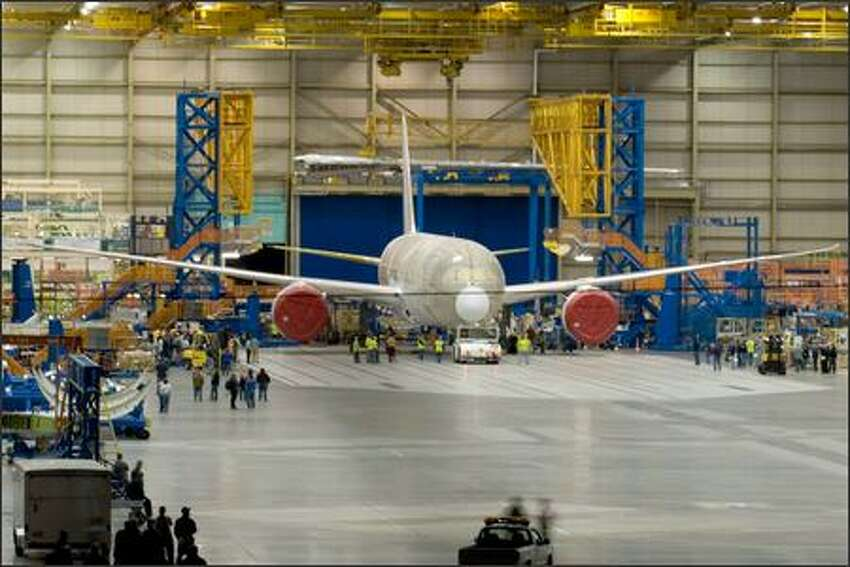 The first 787 Dreamliner sits inside the assembly bay in Everett after the doors were opened around midnight Tuesday, before being rolled outside and moved to a paint facility. Aviation enthusiast and pilot Charles Conklin of Kirkland had picked up hints about the unofficial rollout on an aviation Web site and had waited outside the perimeter of the Boeing property since shortly after 10 p.m. Monday. This was his payoff. (Photo by Charles Conklin)