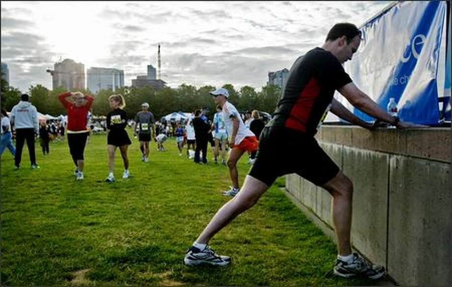 Joe Lake of Mercer Island stretches before the Virginia Mason Team Medicine Marathon/Half Marathon at Seafair in Bellevue. The event also included a marathon relay and 5K run/walk. Nearly 3,400 people participated in the day's events. Photo: Dan DeLong, Seattle Post-Intelligencer