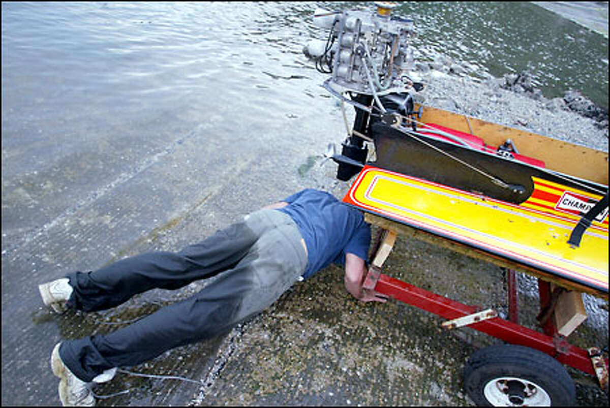 Hydro racer Kit Selig tries to find the source of a leak in his boat the day before the annual race. Most craft aren't built for long-distance racing, so even completing the course is a feat.