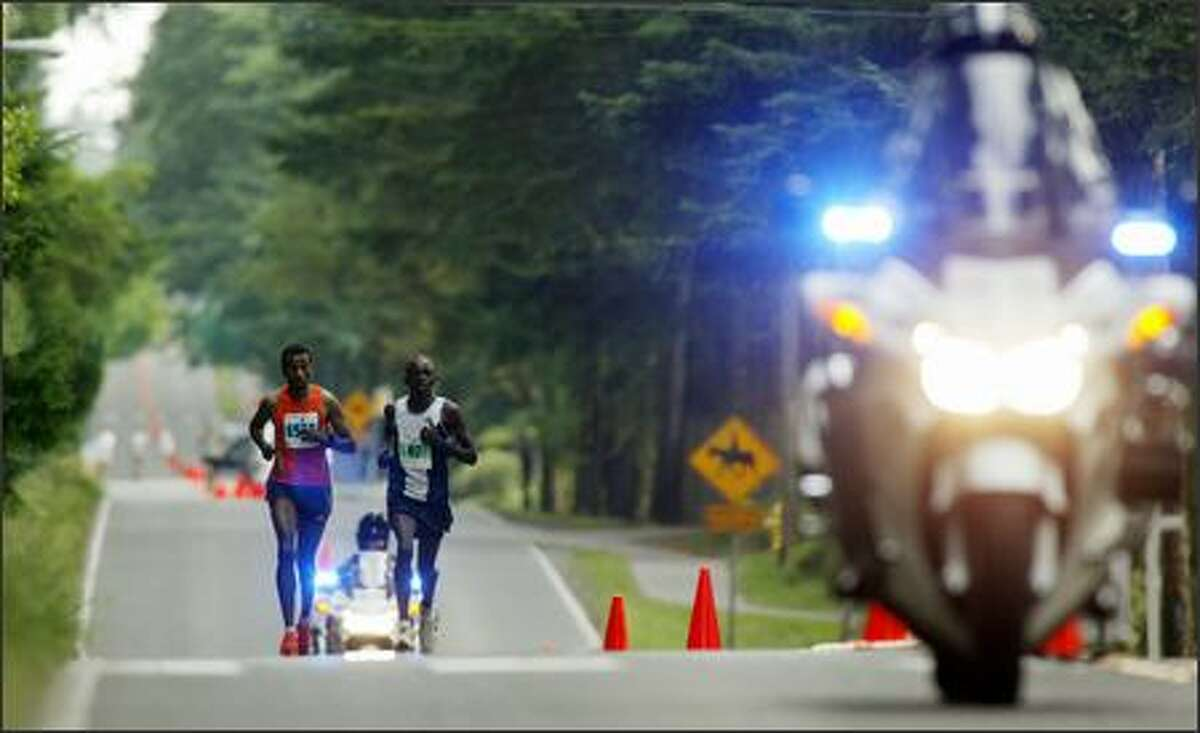 Eventual winner Paul Rugut, 33, of Seattle, right, runs with a member of the marathon relay team Sincere Devotion and Action Team along Bridle Trails State Park during the Virginia Mason Team Medicine Marathon at Seafair in Bellevue.