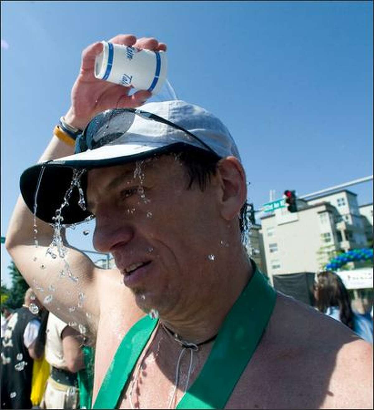 Jonathan Bernard pours a cup of water over his head after finishing the full marathon at the Virginia Mason Team Medicine Seafair Marathon.