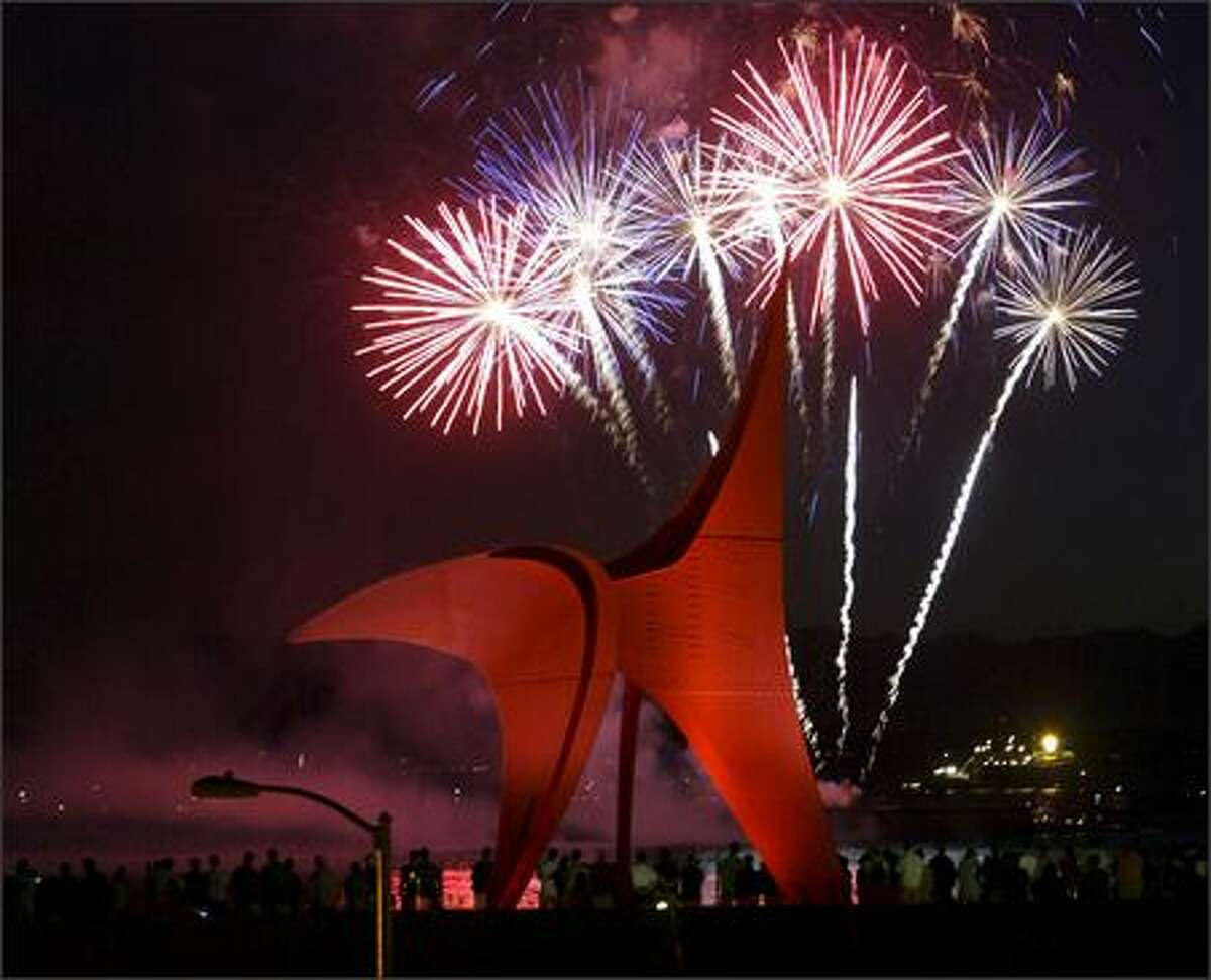 Fireworks explode in the sky over Elliott Bay with Olympic Sculpture Park in the foreground.