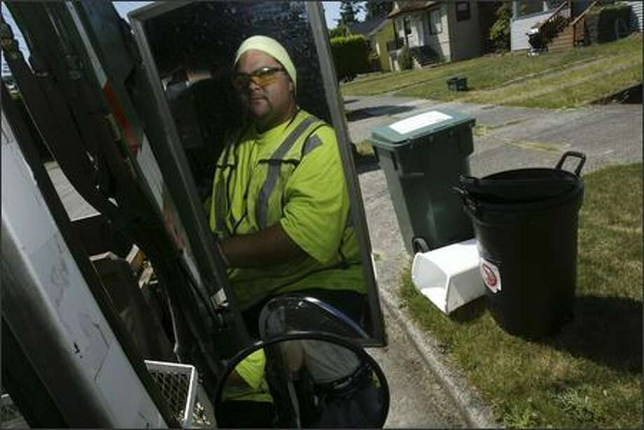 Thomas Masaniai prepares to empty a garbage can on the 600 block of NW 76th St. in Seattle. He then took his truck full of garbage to the transfer station in Wallingford to be compacted and prepared for transit to a landfill near Arlington, Ore. Photo: Andy Rogers, Seattle Post-Intelligencer