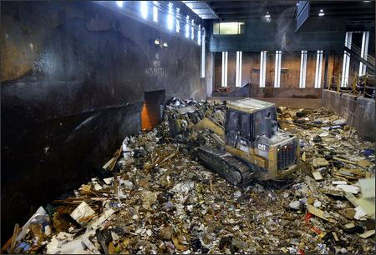 A track loader shoves garbage collected at the transfer station in Wallingford into a compactor.
