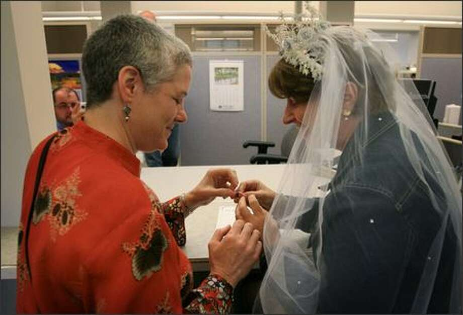Danni Sabia, left, Claudia Wheatley of Olympia exchange rings after registering as domestic partners in Olympia, WA on Monday, July 23, 2007. Photo: Dan DeLong, Seattle Post-Intelligencer