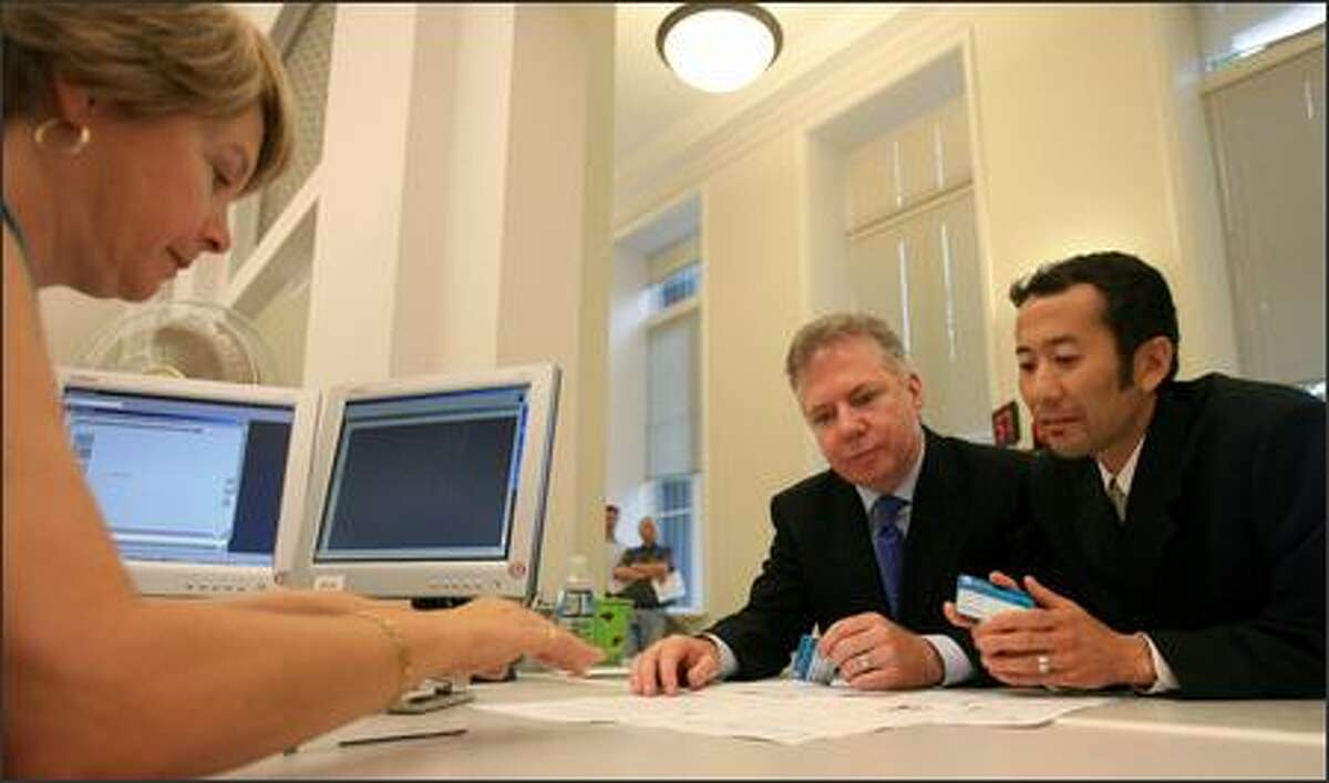 Rep. Ed Murray, D-Seattle, and his partner Michael Shiosaki are helped by D. Ann Peter while they register as domestic partners in Olympia, WA on Monday, July 23, 2007. The two met at a Mount Rainier campground in 1991.