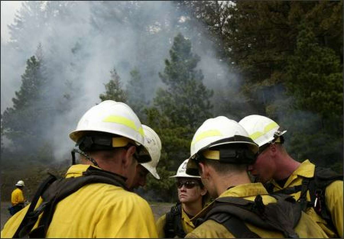A fire crew from the Naches Ranger District discusses the plan as they begin a controlled burn in the Okanagan-Wenatchee National Forest near Naches on Friday May 18, 2007. The burn was to thin dense ground cover to prevent future wild fires as part of a forest management plan.
