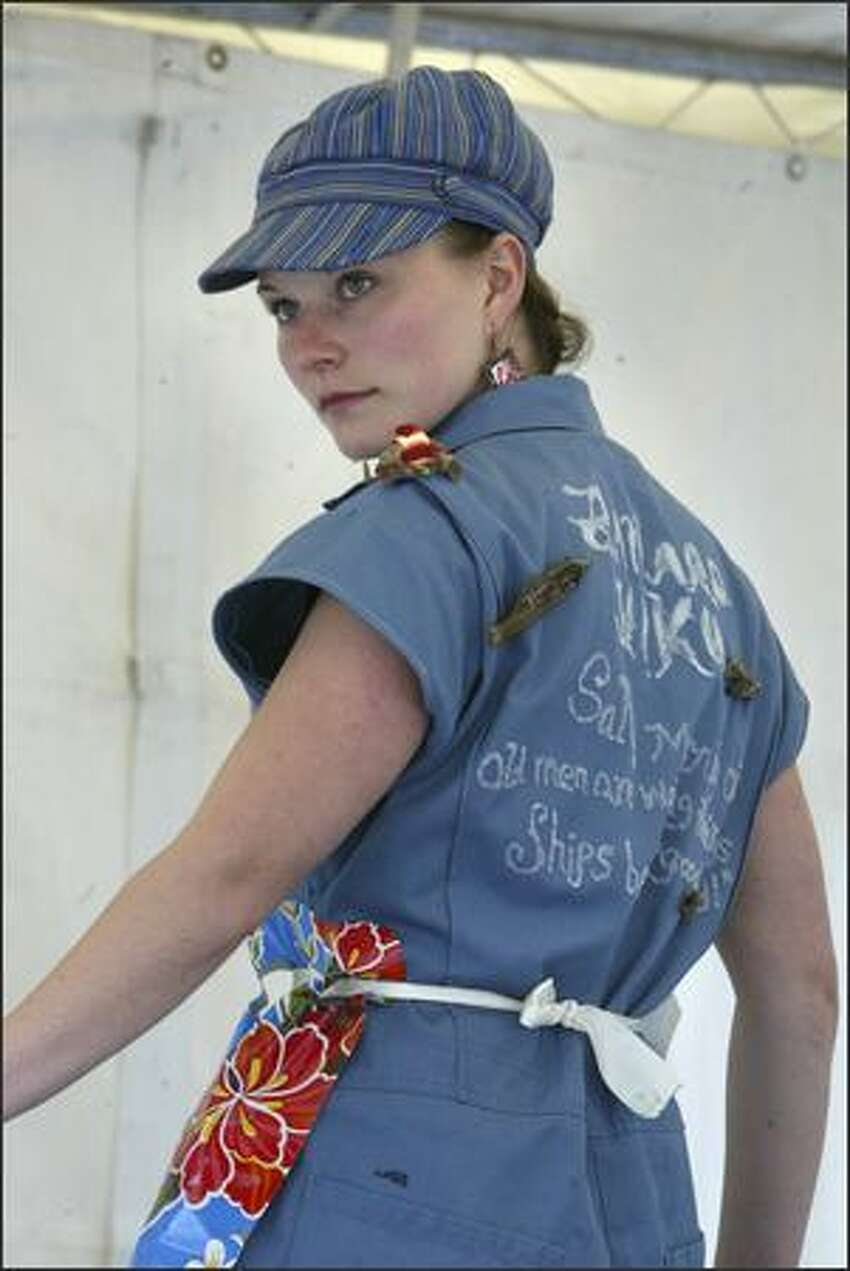 Ciara Griffin, of Ballard, displays her haiku-decorated coveralls for the crowd gathered to see the coverall competition at the 33nd Annual Ballard SeafoodFest.