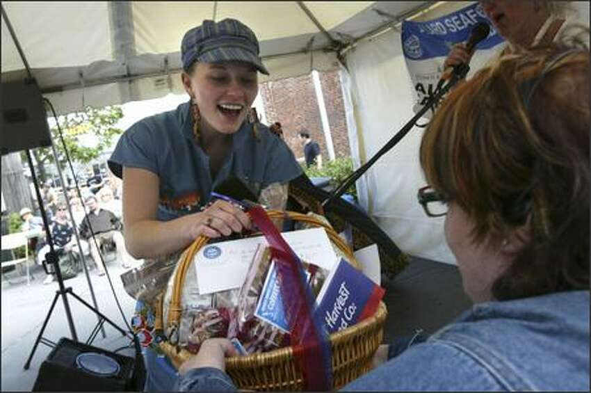 Ciara Griffin of Ballard receives a prize basket from Beth Williamson Miller for her second-place finish in the coverall competition at the 33nd Annual Ballard SeafoodFest.