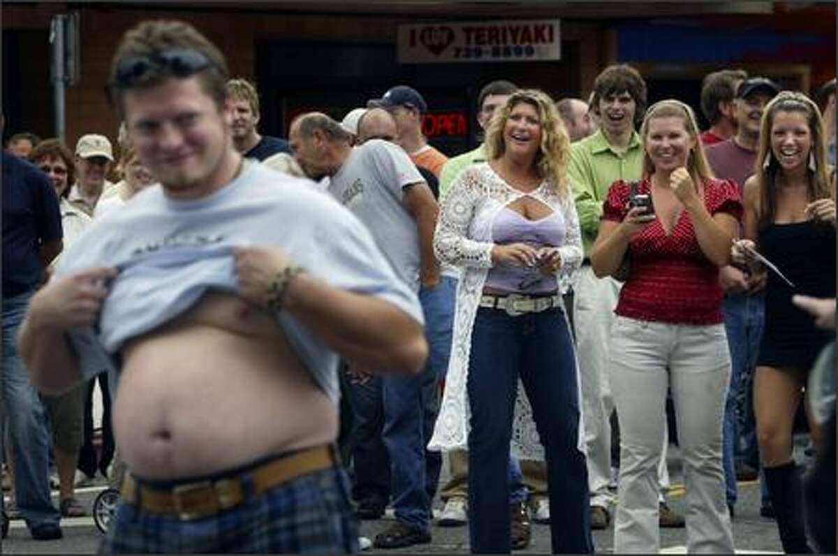 Ryan Carlyle, of Monroe, Wash. shows off his beer belly as Debra Churchill, left, Melissa Olson and Mandy Pemberton, right, of Kirkland cheer during a contest to find the most exceptional belly in the crowd at the Kirkland Classic Car Show.