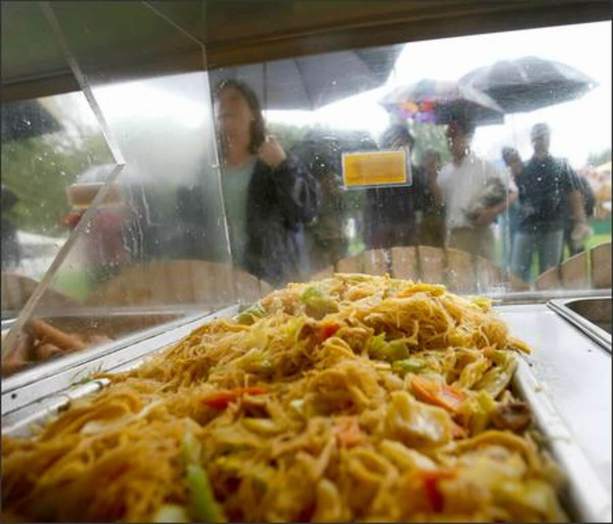 People line up in the rain for Pancit, noodles with vegtable and chicken, served at Espi's at the Bite of Seattle at Seattle Center on Friday.