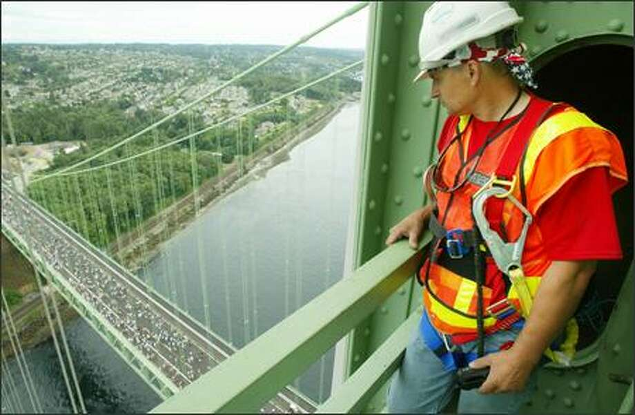 "Steve Hodge, suspension bridge maintenance specialist for the Washington State Dept. of Transportation, has what he calls his ""dream job."" He's presently occupied painting the cables of the old Tacoma Narrows Bridge, but spent Sunday helping media make it to the top of the bridge's tower to give them a perspective on the new bridge and the crowds who came to walk the bridge. Photo: Paul Joseph Brown, Seattle Post-Intelligencer"