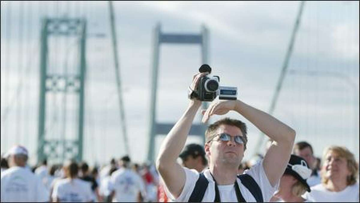 Mike Woods takes video of the new Tacoma Narrows Bridge during the public dedication celebration.