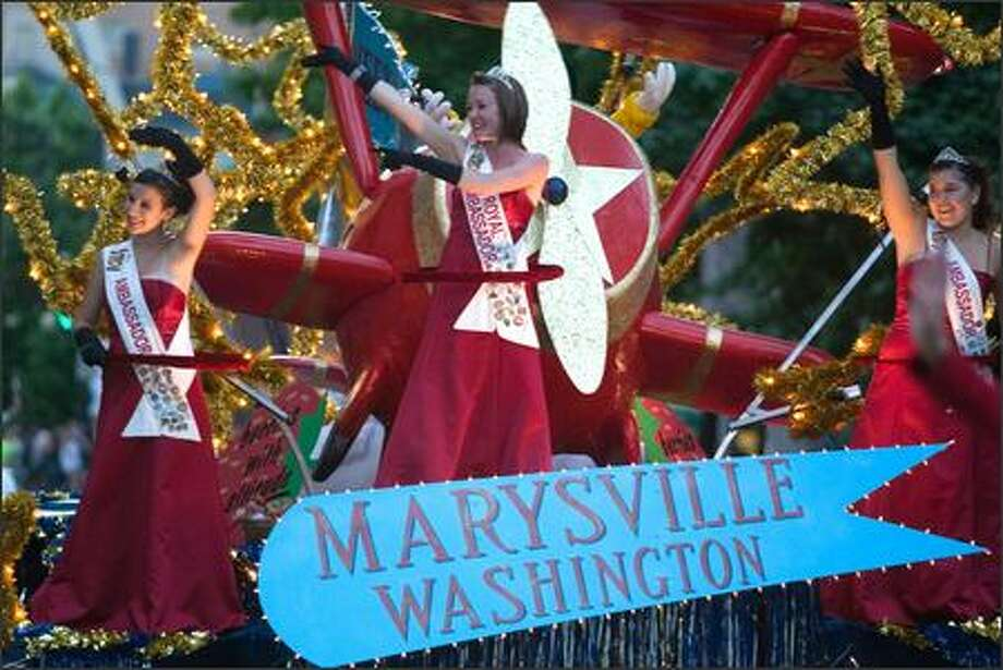 Marysville's float, filled with crimson-clad ambassadors, waves to the crowd during the 58th annual Seafair Torchlight Parade through downtown Seattle. Photo: Jim Bryant, Seattle Post-Intelligencer