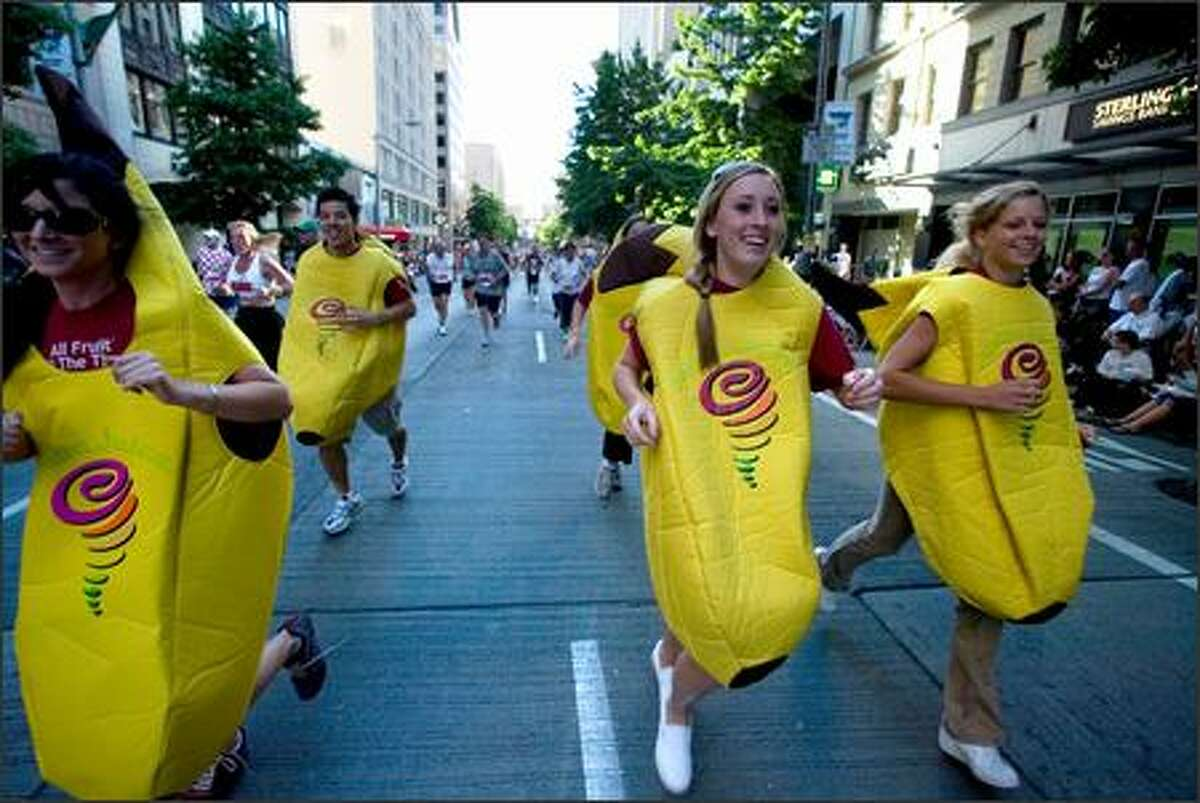 A group of runners dressed in banana suits promoting the Jamba Juice chain takes part in the Torchlight Run at the 58th annual Seafair Torchlight Parade.