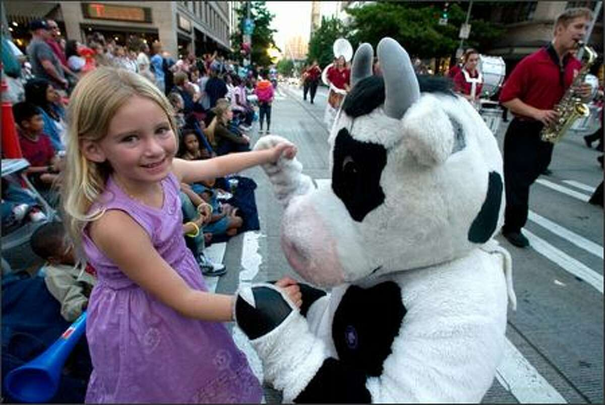 Kendall Carey, left, dances with the Puyallup cow during the 58th annual Seafair Torchlight Parade.
