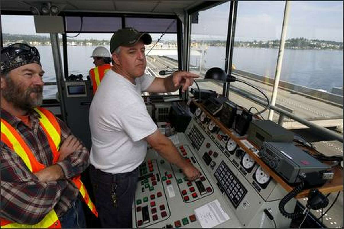 Chuck Mikesell, center, points out the views of cameras on the bridge as he opens the bridge as Gerald Connell, left, and Ron Paananen (rear) survey the scene.