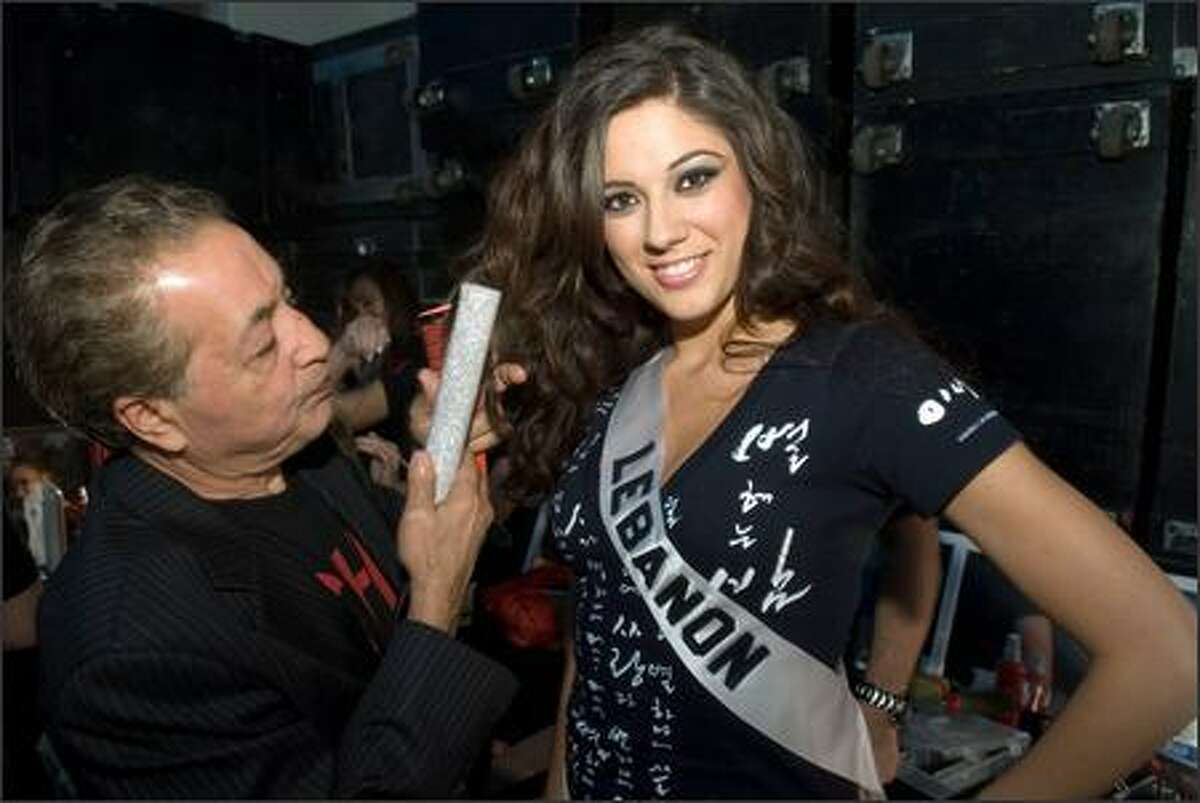 A hairstylist styles the hair of Nadine Njeim, Miss Lebanon 2007, before the broadcast of the 2007 Miss Universe competition from the Auditorio Nacional in Mexico City.