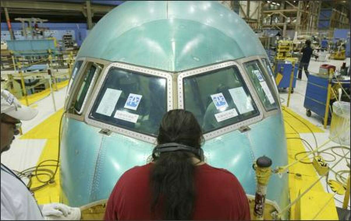 David Farley, left, and Roger Herrera work on the nose of a Boeing 767 Tanker prior to a rally organized by the company to thank employees and help raise awareness of the advantages of the plane on Monday.