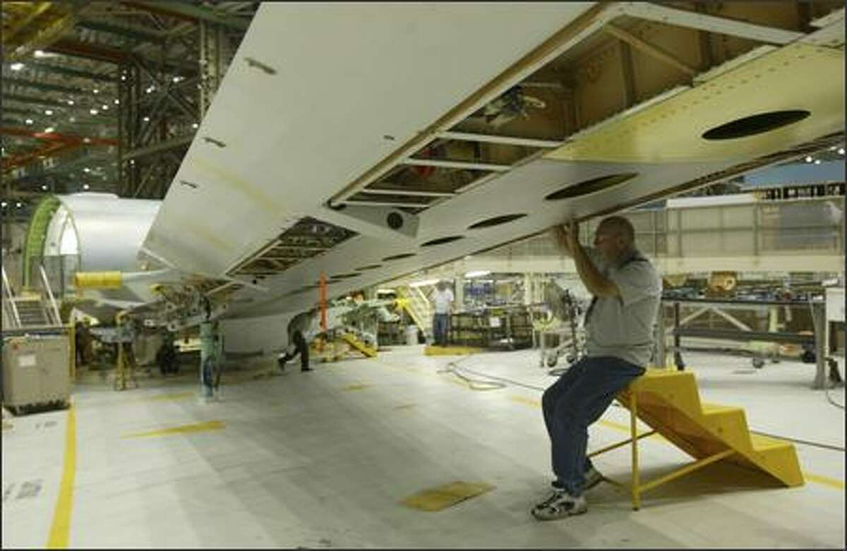 Tracy Thompson works on the wing of a Boeing 767 Tanker prior to a rally organized by the company to thank employees and help raise awareness of the advantages of the plane on Monday.