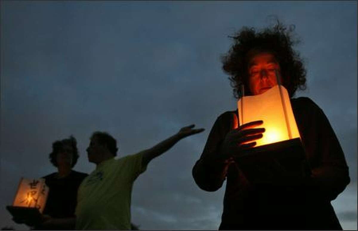 Cora Mackoff (right) protects her lantern from the wind as Karen Tarr and Bob Trutnau wait to launch their lanterns into the waters of Greenlake during the Hiroshima to Hope event held at Greenlake Park in Seattle on Monday.