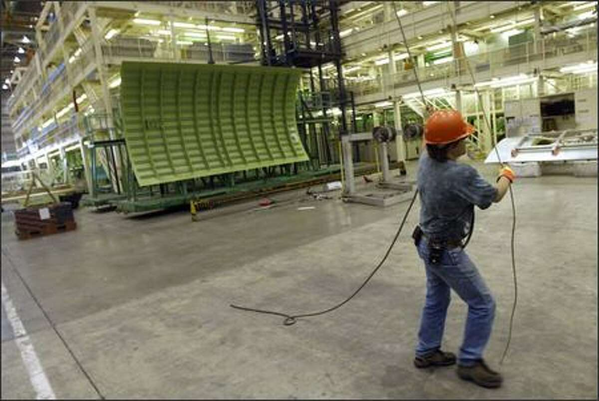 A Boeing employee uses a rope to haul machinery used in production of the Boeing 767 Tanker at the Everett factory on Monday.