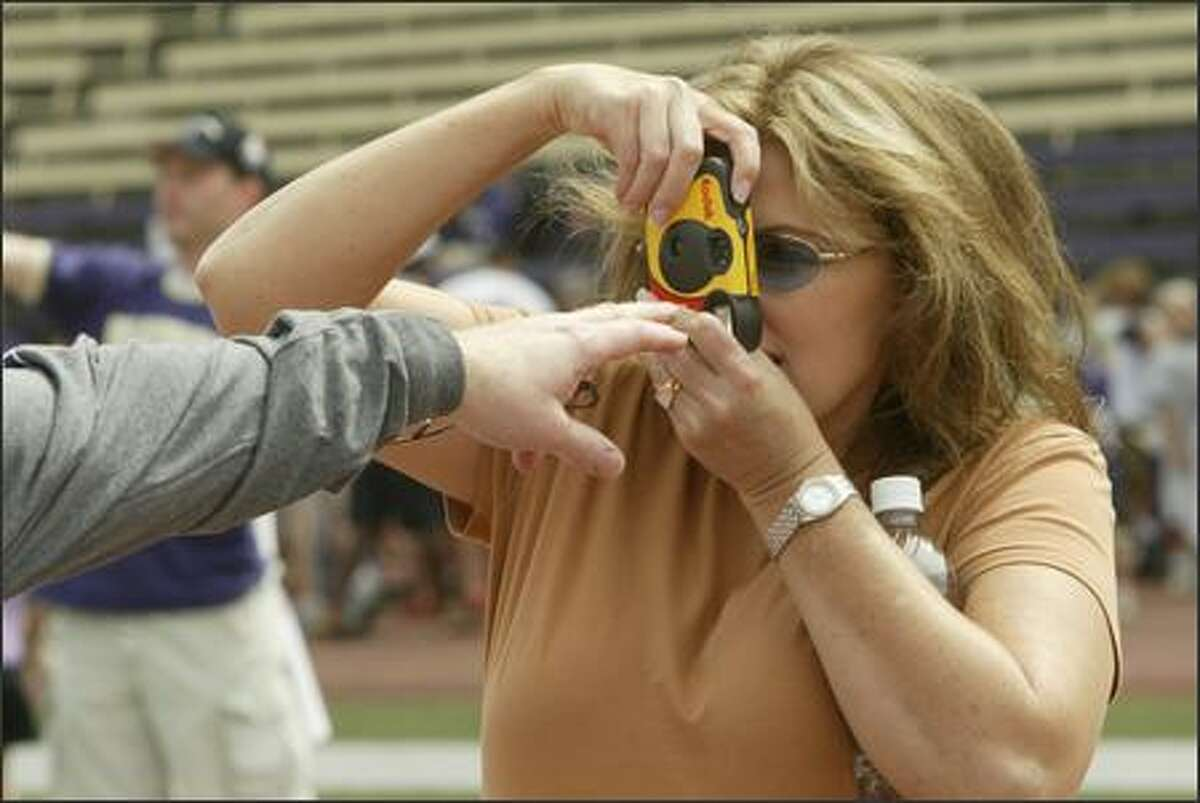 Renae Hoon gets a little advice on how to make the photo from her husband, Ron, as she tries to make a photo of him in Husky Stadium during Husky Picture Day.