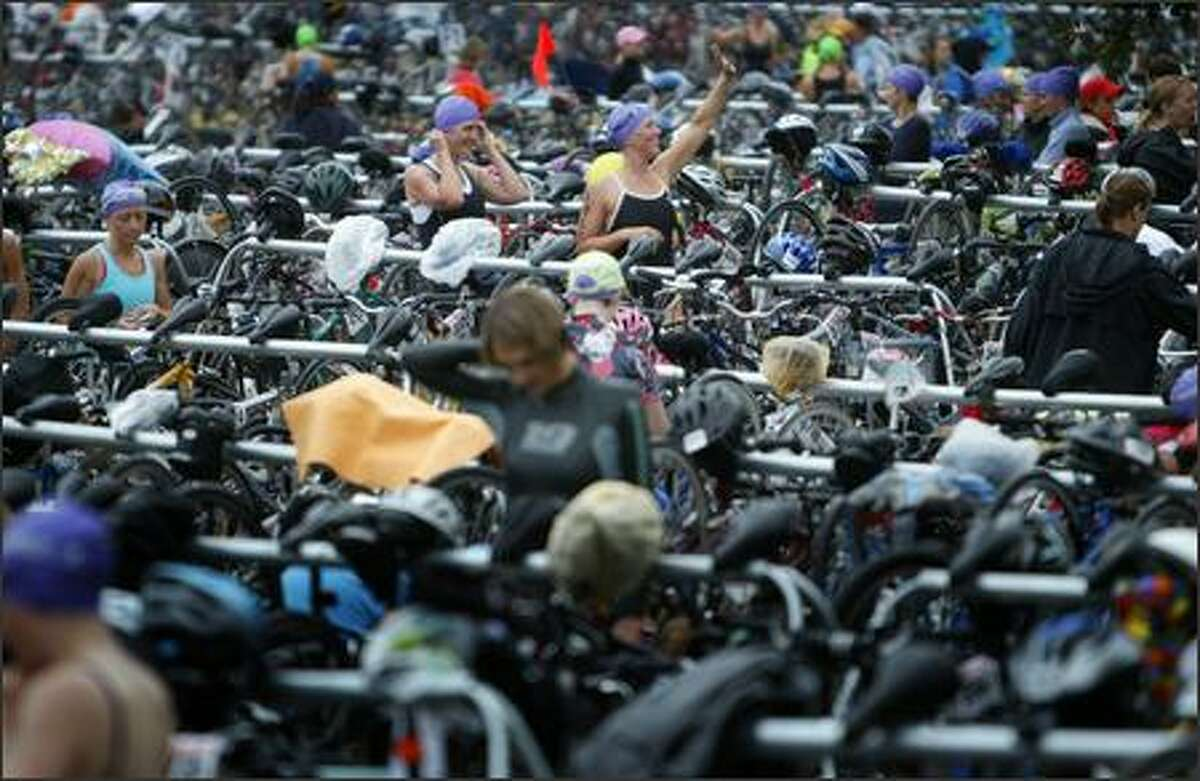 Danskin Women's Triathlon participants wander through a sea of bicycles and equipment at Genesee Park in Seattle.
