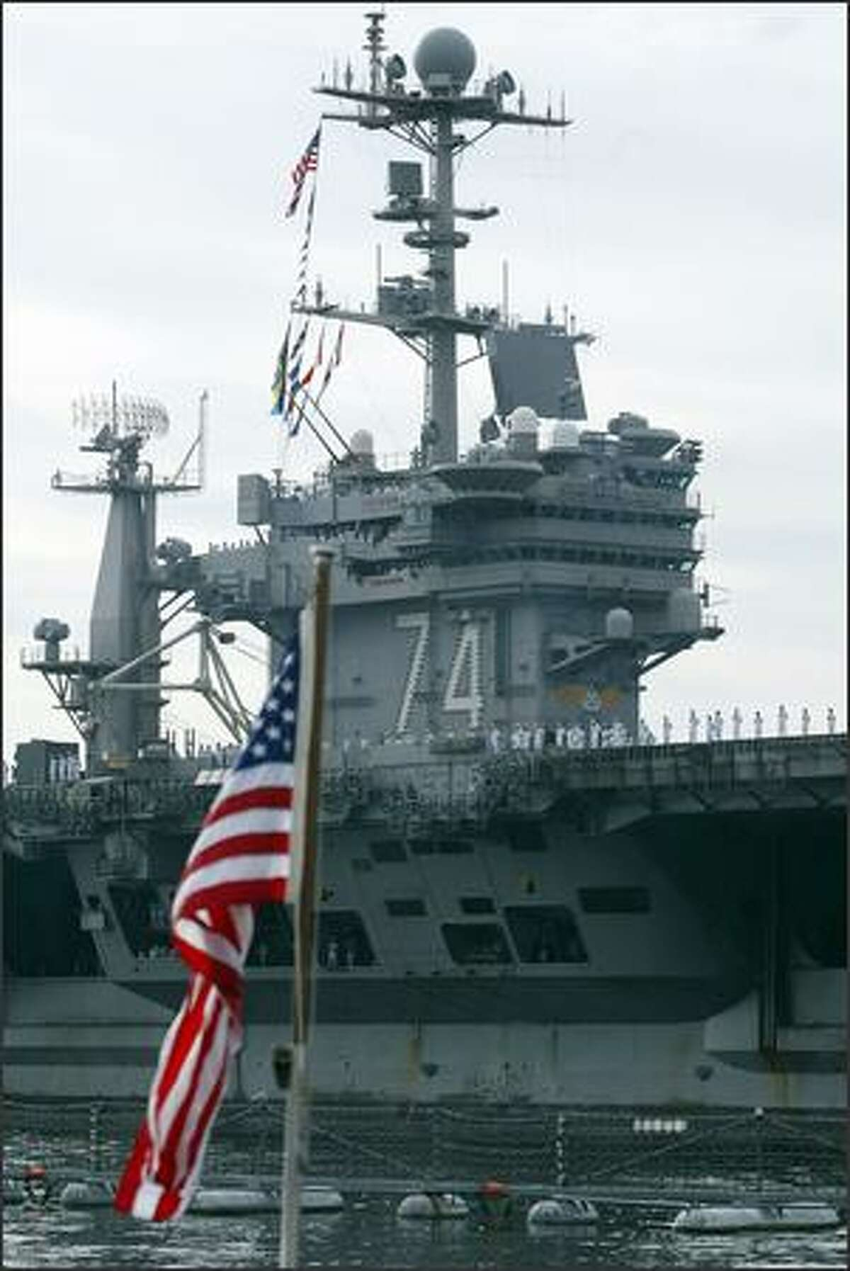 The superstructure of the USS Stennis passes before the flag on the submarine USS Seawolf at the Naval Base Kitsap in Bremerton, Wash., Friday August 31, 2007. The Stennis returned to its home port after a half-year deployment in the waters of the Middle East in support of the fighting in Afghanistan and Iraq.