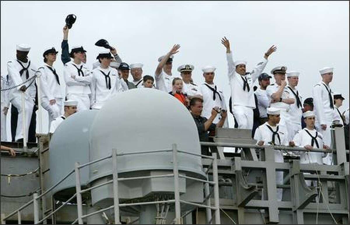 Sailors wave to family members from the deck of the USS Stennis as it docks at the Naval Base Kitsap in Bremerton, Wash., Friday August 31, 2007. The Stennis returned to its home port after a half-year deployment in the waters of the Middle East in support of the fighting in Afghanistan and Iraq.