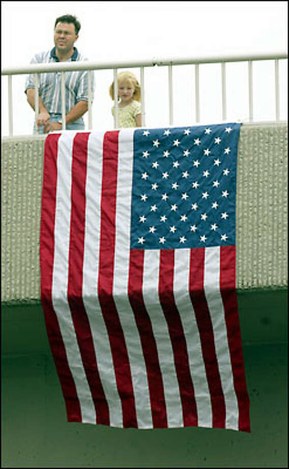 Rob Minor, of Covington, and his daughter Melissa raised a flag on the Covington Way SE overpass near the scene of an accident that killed D.O.T. worker Jake Baardson last week on Highway 18. About 150 vehicles made their way convoy-style from Baardson's memorial service in Kent to the site near Covington. Photo: Mike Urban, Seattle Post-Intelligencer