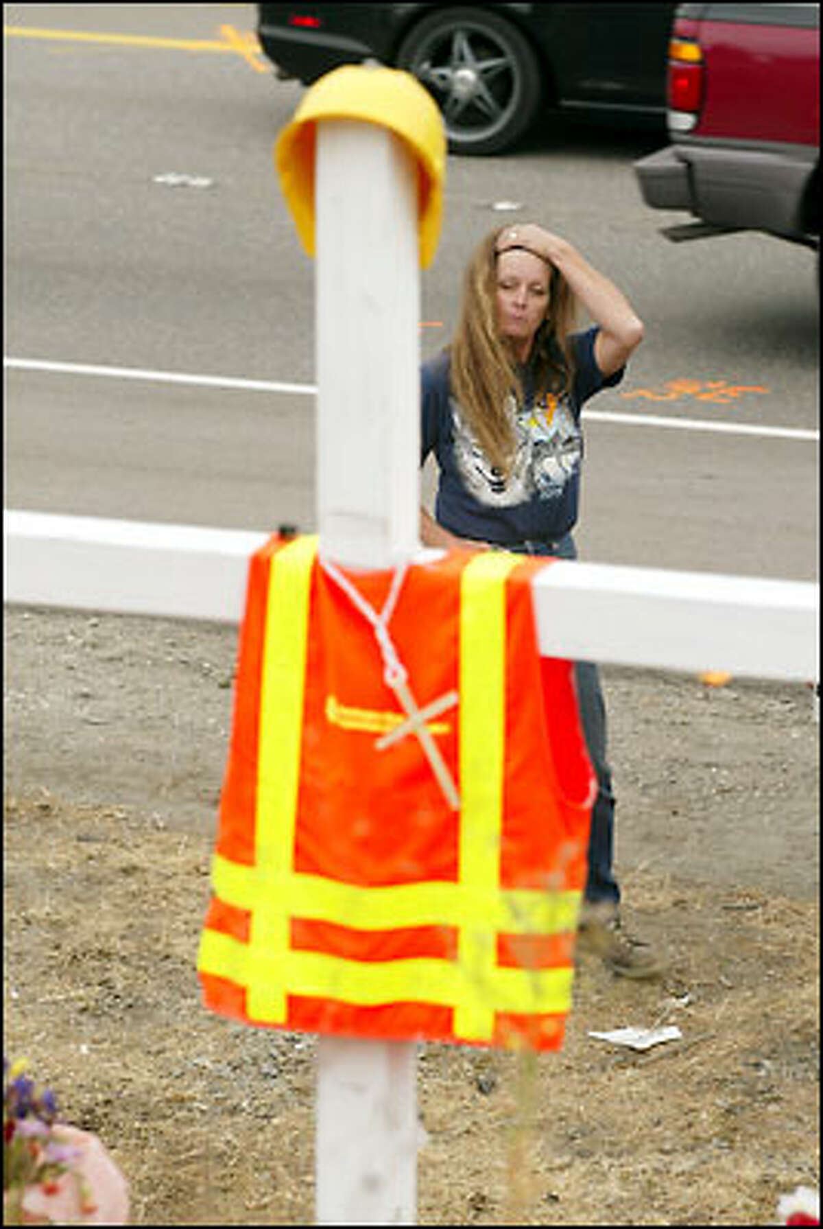 Washington State D.O.T. worker Esther Paokovich, whom Jake Baardson trained, mourns at the scene of the accident that killed Baardson last week on Highway 18. Paokovich witnessed the accident and called 911.