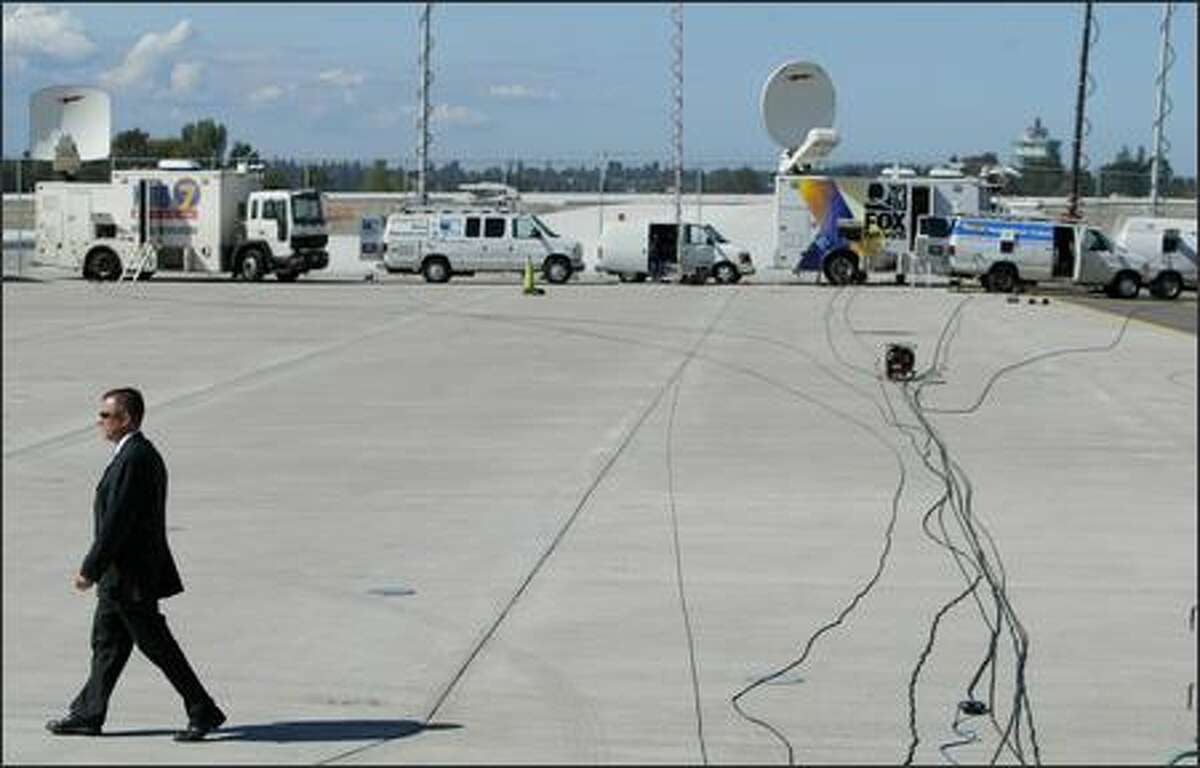 An advance team member walks across the tarmac and the cables bringing President George W. Bush's visit to a live audience at SeaTac Airport on Monday, August 27, 2007.