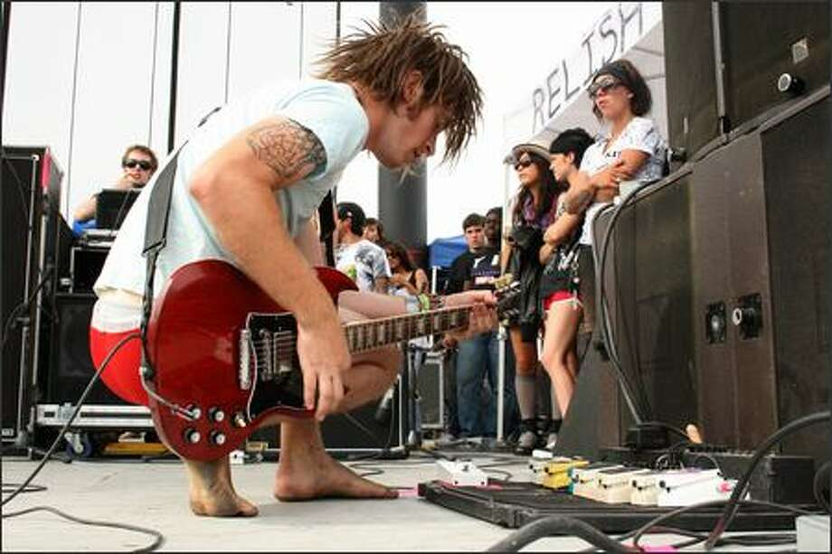 Jason Hale of Chiodos tests his effects pedals between songs at the Warped Tour on Saturday. Photo: Alli Curtis, Special To The P-I