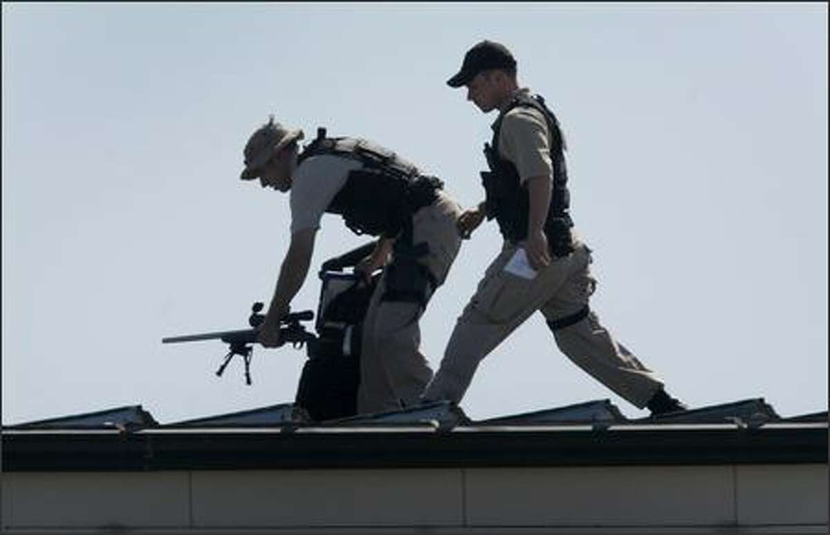 A security team for U.S. President George W. Bush sets up atop a hanger at SeaTac Airport on Monday, August 27, 2007.