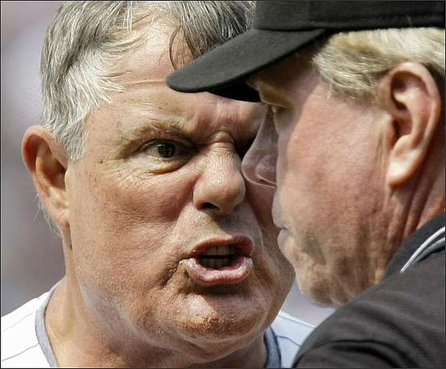 Chicago Cubs manager Lou Piniella, left, argues with third base umpire Brian Gorman, right, after first base umpire Rob Drake ejected Piniella during the ninth inning of their baseball game against the Florida Marlins at Wrigley Field in Chicago. (AP Photo/Charles Rex Arbogast)