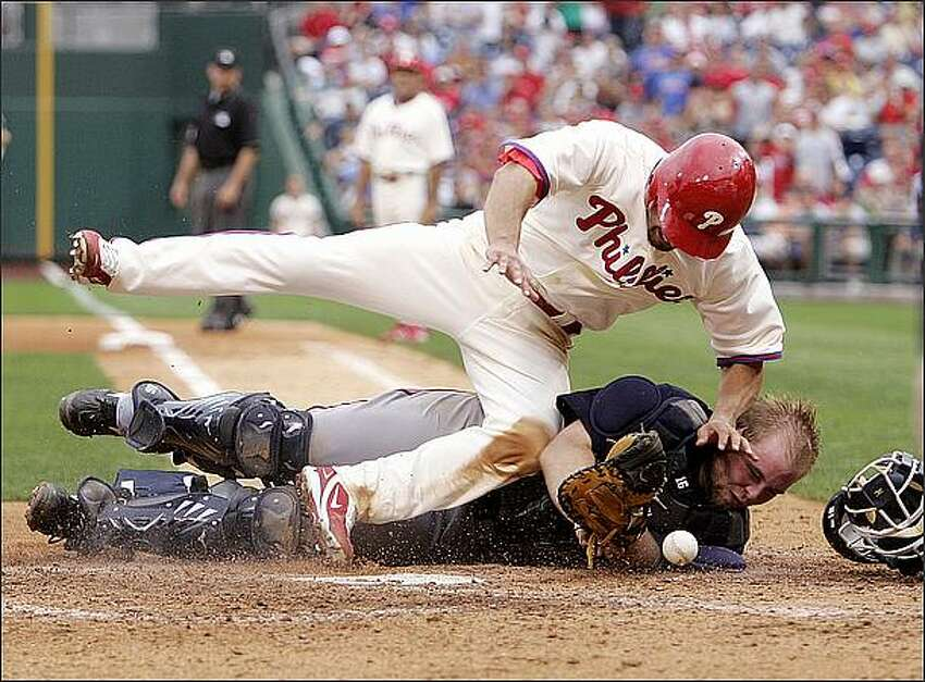 Philadelphia Phillies' Shane Victorino, top, collides with Atlanta Braves' Brian McCann as he scores on Ryan Howard's two-run single in the sixth inning of a baseball game in Philadelphia. McCann was injured and left the game. (AP Photo/Tom Mihalek)wbb