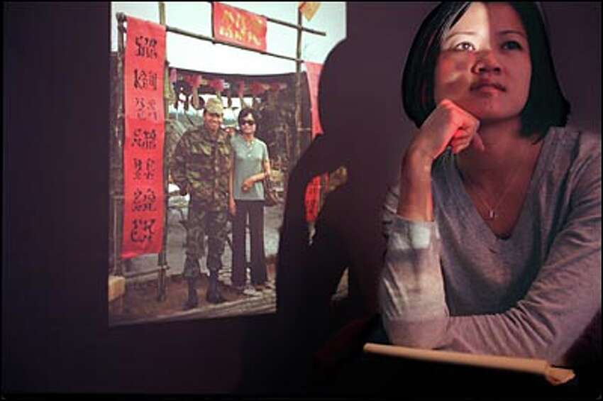 Phuong Le reflects on a projected photograph of her parents, Le Van Me and Sen Le, taken in 1973 at a South Vietnamese army camp called Happy Valley. Her parents were celebrating Tet, the Lunar New Year.
