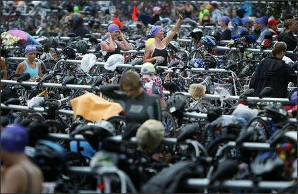 Danskin Women's Triathlon participants wander through a sea of bicycles and equipment.