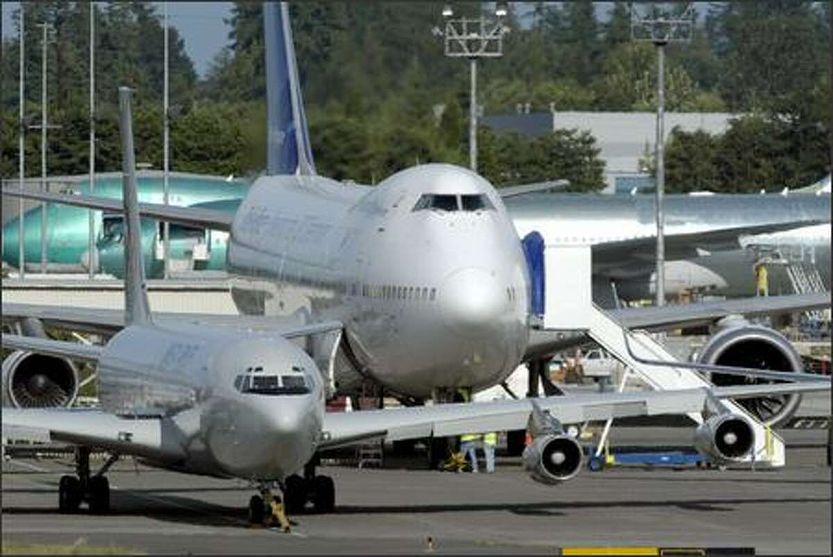 A Boeing 747-200 dwarfs the 707 Omega tanker as they wait at Everett's Paine Field before flying to Boeing Field in Seattle.
